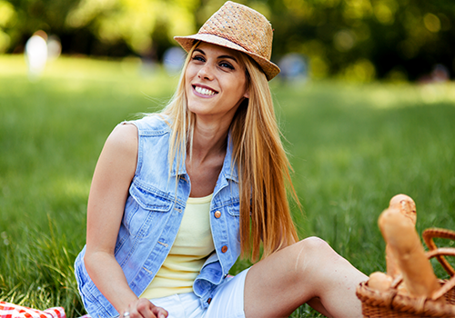 Blonde woman wearing jean vest and straw hat smiles with picnic basket