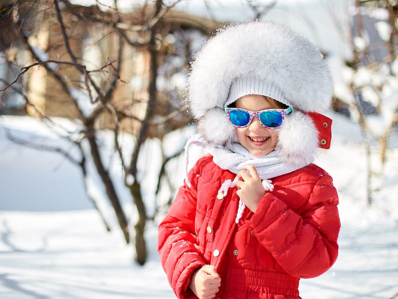 Happy laughing toddler girl wearing a red down jacket and white knitted hat and scarf