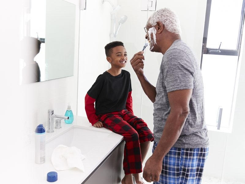Man Pajamas In Bathroom Shaving Whilst Young man Watches